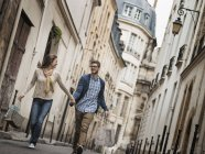 Couple walking along narrow street in historic city with shopping bags. — Stock Photo
