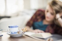 Cup and saucer with croissant on table with woman reading book in background. — Stock Photo