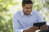 Mid adult man using digital tablet while sitting in city park. — Stock Photo