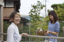 Two Japanese women standing in garden with potted plants. — Stock Photo