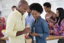 Man and woman holding wine glasses at party with people in background. — Stock Photo