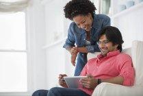Мужчина на диване и стоящая женщина смотрит на цифровой планшет в офисе . — стоковое фото