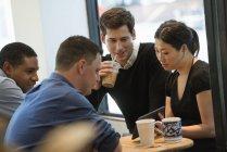 Gruppo di amici che bevono caffè nella caffetteria e utilizza la compressa di digital. — Foto stock