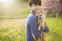 Young woman holding and hugging chihuahua dog on grass field in park. — Stock Photo