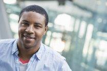 Uomo afroamericano in camicia blu in piedi di fronte a un edificio moderno . — Foto stock