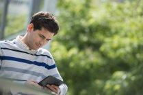 Junger Mann stützte sich auf Geländer im Park und Verwendung von digital-Tablette — Stockfoto