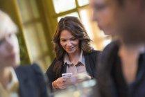 Joven sentado en mesa y uso de smartphone con personas en primer plano - foto de stock