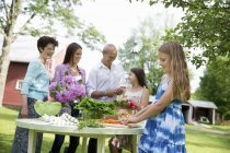 Family gathering around table and preparing fresh vegetables and fruits. — Stock Photo