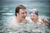 Père et fils rire dans l'eau de piscine. — Photo de stock