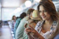 Женщина смотрит на смартфон с ряда клиентов в закусочной кафе — стоковое фото