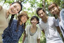 Low angle view of Japanese friends posing and embracing in forest. — Stock Photo