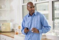 Homem de camisa azul segurando smartphone e xícara de café na cozinha do escritório . — Fotografia de Stock
