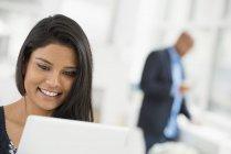 Крупный план молодой женщины, использующей цифровой планшет на офисном рабочем месте . — стоковое фото