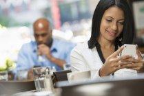 Frau lächelt mit Smartphone am Kaffeetisch, Mann trinkt im Hintergrund. — Stockfoto