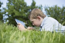 Elementary age boy lying on grass and using digital tablet. — Stock Photo