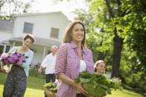 Family walking across lawn carrying flowers, vegetables and fruits. — Stock Photo