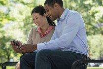 Середині дорослий чоловік і жінка за допомогою смартфона разом в міському парку. — стокове фото