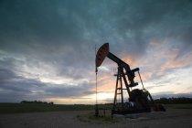 Derrick d'huile avec pompe à puits silhouette contre le ciel du soir au Canada . — Photo de stock
