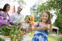Girl holding fresh carrots with family at garden table in countryside. — Stock Photo