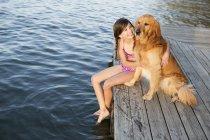 Попередньо підлітків дівчина в Купальники з золотистий ретрівер собака, сидячи на пристані на озера. — стокове фото