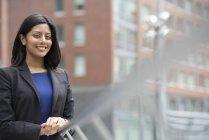 Jovem mulher de vestido azul e jaqueta cinza encostada no corrimão de rua e olhando na câmera . — Fotografia de Stock