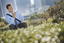 Young man sitting on park bench, smiling and using mobile phone. — Stock Photo