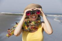 Donna in cappello da sole e sciarpa con binocolo sulla spiaggia del New Jersey Shore, USA . — Foto stock