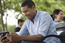 Man sitting on bench and using digital tablet with woman talking on phone in background. — Stock Photo