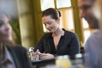 Mid adult woman sitting at bar table and using smartphone with people in foreground. — Stock Photo
