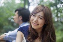 Joven sonriente y mirando en la cámara mientras está sentado con el hombre en el Parque. - foto de stock