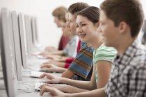 Gruppe von Jungen und Mädchen im Computerkurs arbeitet an Monitoren. — Stockfoto