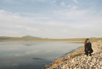 Woman collecting pebbles on shore of mountain lake. — Stock Photo