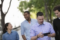 Four people walking on street and mid adult man using digital tablet. — Stock Photo