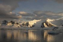 Dusk and flat calm water of shore of mountain landscape in Antarctica. — Stock Photo