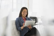 Woman using digital tablet on comfortable chair in modern office interior. — Stock Photo