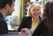 Cheerful women and man sitting in bar with drinks and talking. — Stock Photo