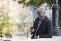 Empresario con traje y corbata revisando el teléfono mientras se apoya en el poste de luz en la calle . - foto de stock