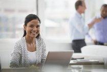 Junge Frau beim Sitzen am Schreibtisch mit Laptop-Computer mit Männern reden im Hintergrund lächelt — Stockfoto