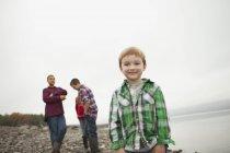 Adolescentes e o menino de idade elementar em pé na praia. — Fotografia de Stock