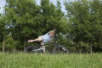 Elementary age boy falling off bicycle and overbalancing in grassy field. — Stock Photo