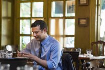 Man sitting at bar table alone and checking smartphone. — Stock Photo