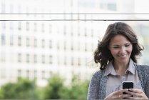 Geschäftsfrau in grauer Strickjacke nutzt Smartphone in der Stadt. — Stockfoto