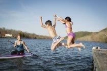 Kinder Springen ins Wasser vom Bootssteg mit Frau Paddleboard beobachten — Stockfoto