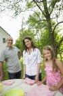 Vater und Töchter stehen am Gartentisch. — Stockfoto