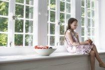Mädchen im Grundalter sitzt auf Fensterbank mit Obstschale. — Stockfoto