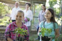 Girls holding young plants in pots with mature couple and young woman in background at farm. — Stock Photo
