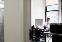 Hombre maduro sentado en oficina y ordenador - foto de stock