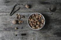 Bol de noix mélangées, de coquilles et de casse-noisette sur table. — Photo de stock