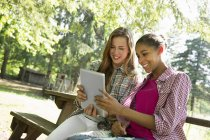 Two girls sitting outdoors on bench and using digital tablet. — Stock Photo
