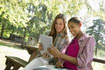 Duas meninas ao ar livre sentado no banco e usando tablet digital — Fotografia de Stock